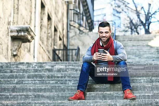 Junger Mann Lächeln und Tippen auf der Treppe