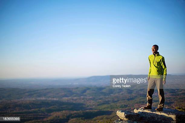 A young man smiles while standing on an boulder at the top of Cheaha Mountain.