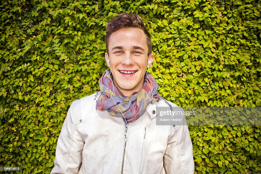 A young man smiling and using headphones : Stock Photo