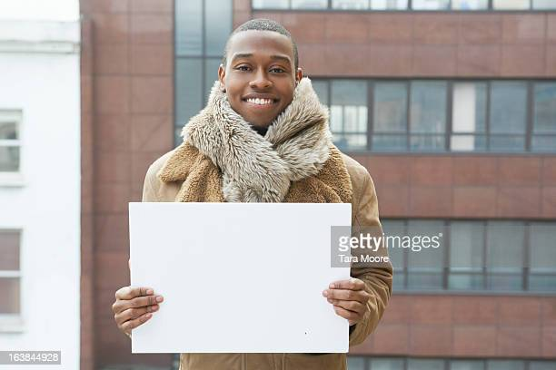 young man smiling blank sign