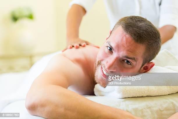 Junger Mann Lächeln während entspannende spa-massage