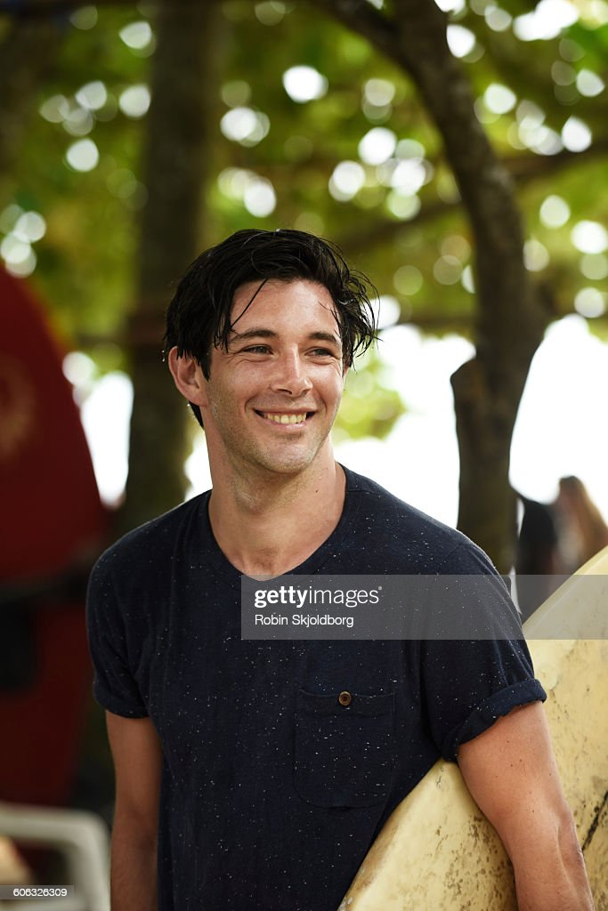 Young Man smiling  holding surfboard