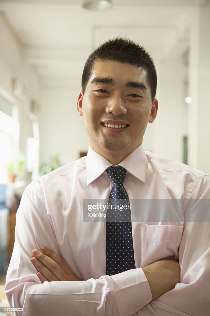 Young man smiling in the office, portrait : Stock Photo