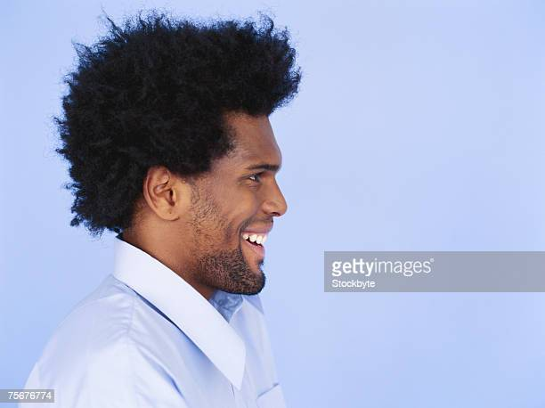Young man smiling, looking away, close-up, side view