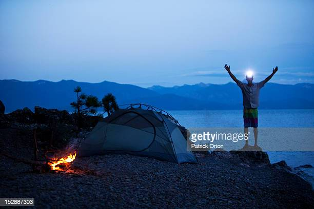 A young man smiling next to a campfire and tent on a camping trip with a head light on in Idaho.