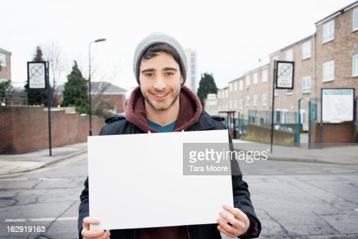 young man smiling to camera holding blank sign