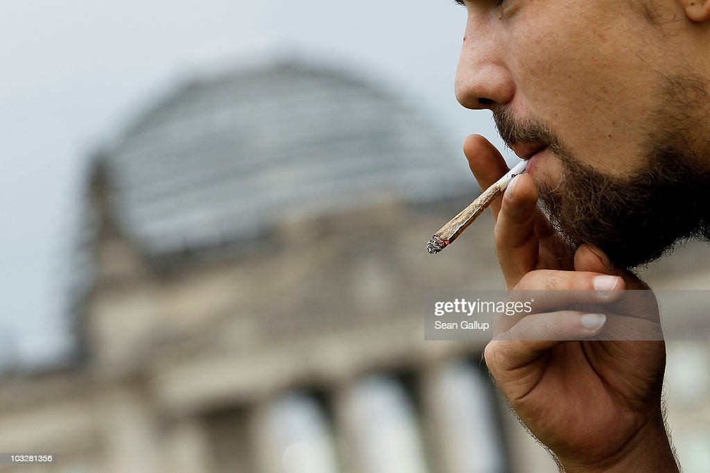 A young man smokes a marijuana joint in front of the Reichstag following the annual Hemp Parade, or 'Hanfparade,' in support of the legalization of marijuana in Germany on August 7, 2010 in Berlin, Germany. The consumption of cannabis in Germany is legal, though all other aspects, including growing, importing and selling it, are not. However, since the introduction of a new law in 2009, the sale and possession of marijuana for licenced medicinal use is legal.