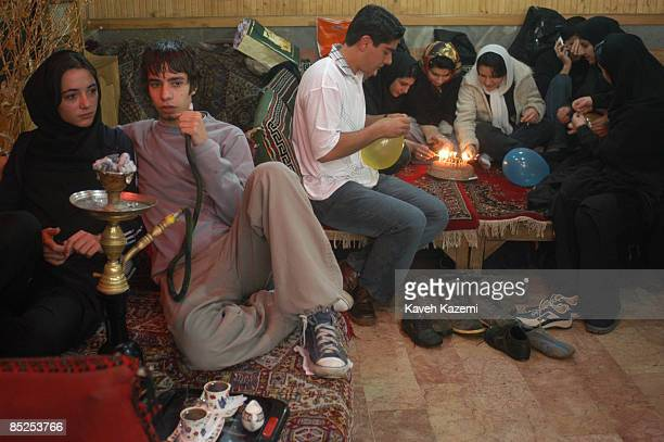 A young man smoking a waterpipe sits with his girlfriend in a teahouse in Darband in the foothills of northern Tehran 19th March 2004 People go to...
