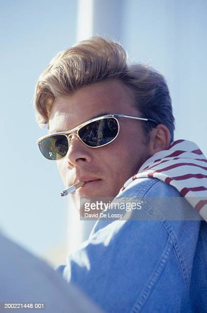 Young man smoking cigarette, portrait