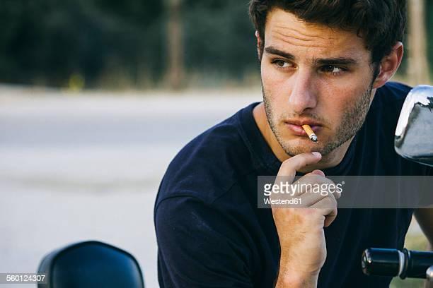 Young man smoking sitting on his motorbike