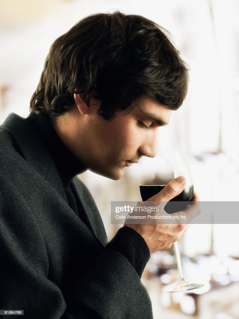Young man sniffing glass of wine : Stock Photo