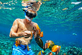 Happy family vacation - man in snorkeling mask dive underwater with tropical fishes in coral reef sea pool. Travel lifestyle, water sport outdoor adventure, swimming lessons on summer beach holiday