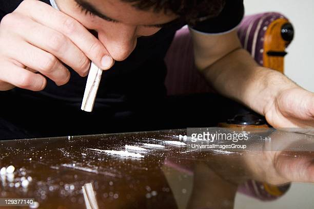 Young man snorting cocaine through rolled up banknote