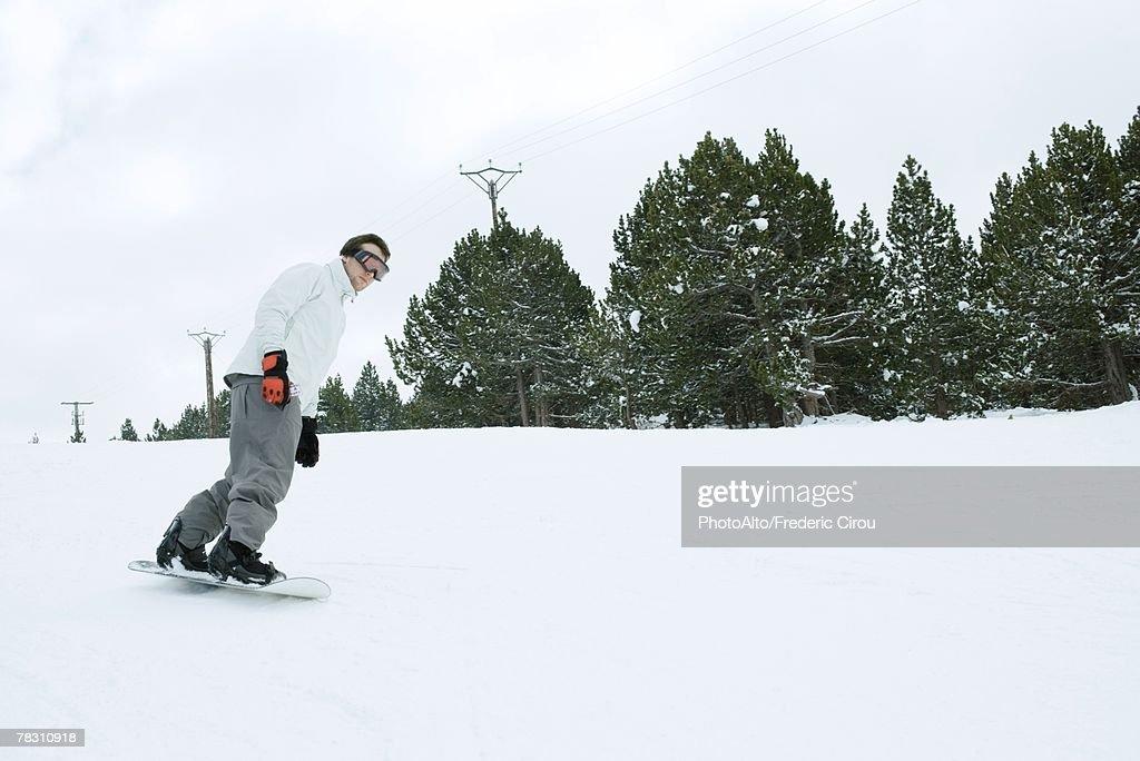 Young man snowboarding, full length : Stock Photo