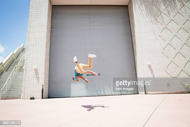 Young man somersaulting, a parcour runner on the street