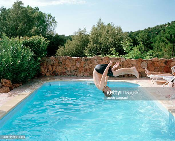 Young man somersaulting into swimming pool