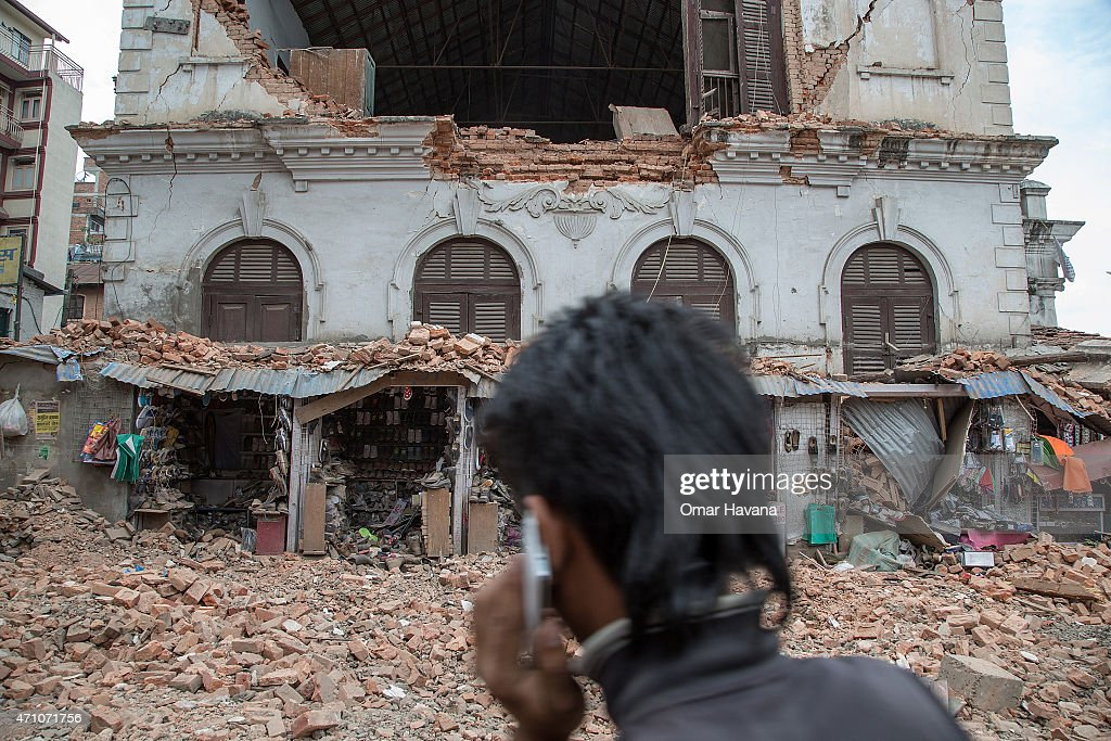 A young man speaks on the phone in front of a collapsed building in the city center following an earthquake on April 25 2015 in Kathmandu Nepal A...