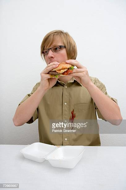 Young man spilling ketchup on his shirt whilst eating a hamburger