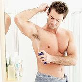 young man spraying deodorant