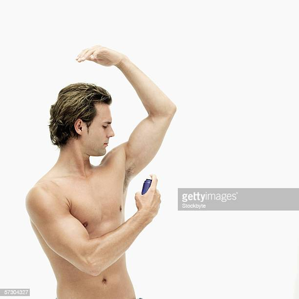 Young man spraying deodorant under his arm