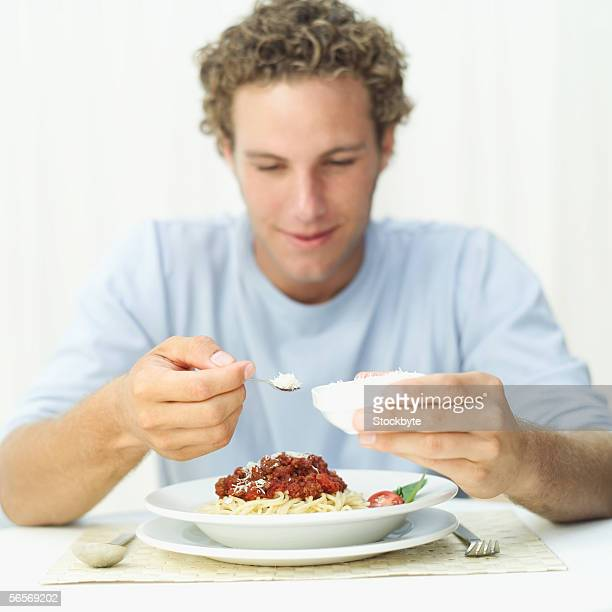 young man sprinkling grated cheese onto spaghetti in a bowl