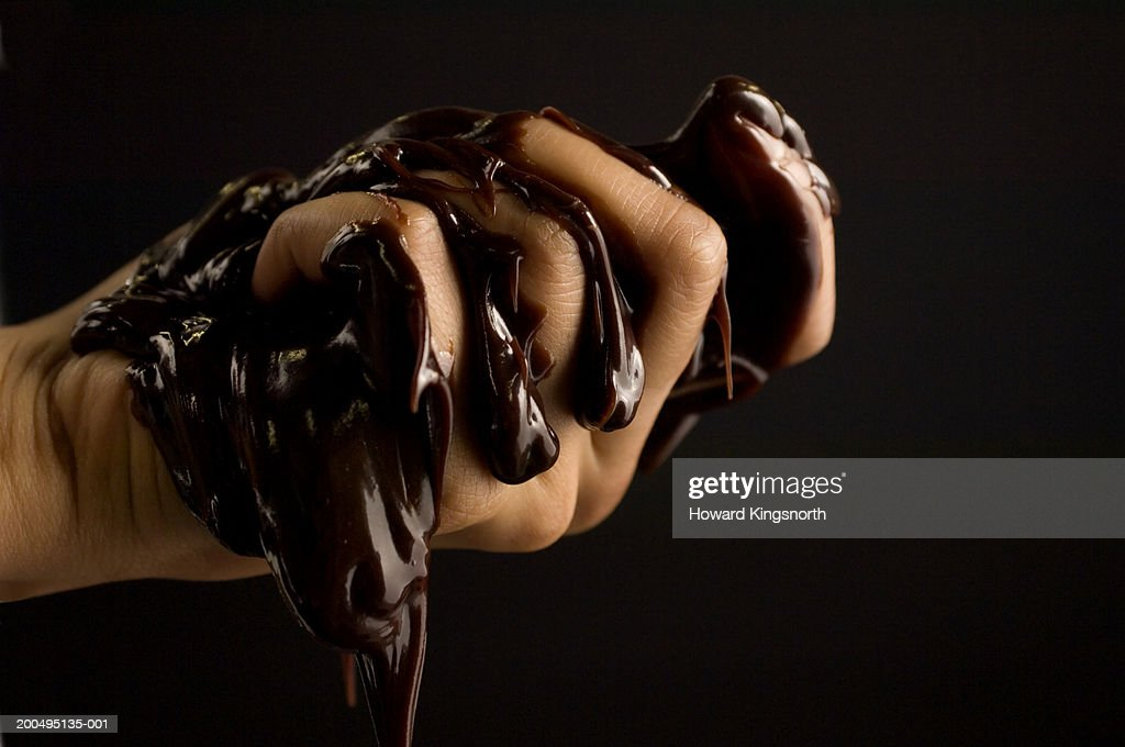 Young man squeezing melted chocolate, close-up of hand : Stock Photo