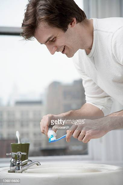 Young man squeezing toothpaste out of tube