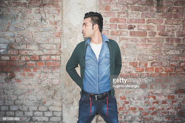 Young man standing against brick wall