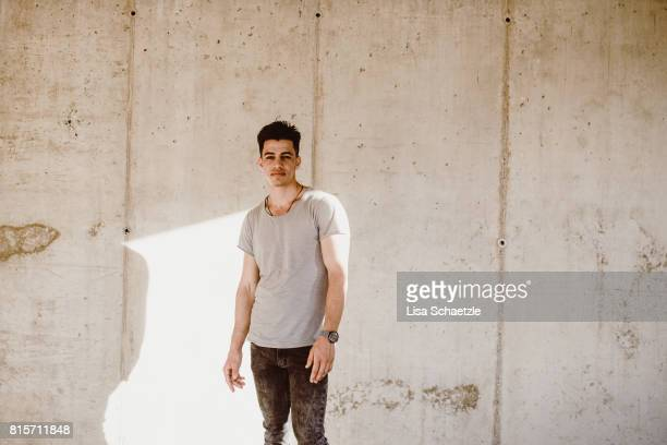 Young Man standing against wall