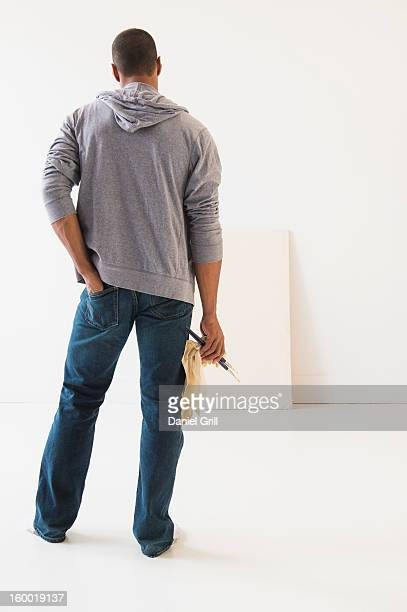 Young man standing against white canvas