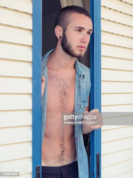 Young Man Standing Amidst Sliding Door