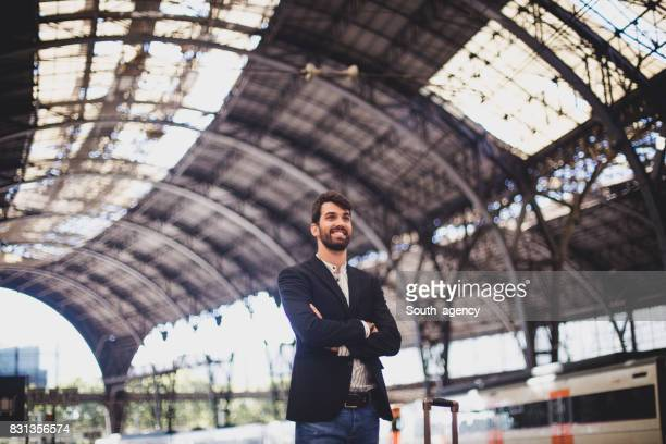 Young man standing at railroad station