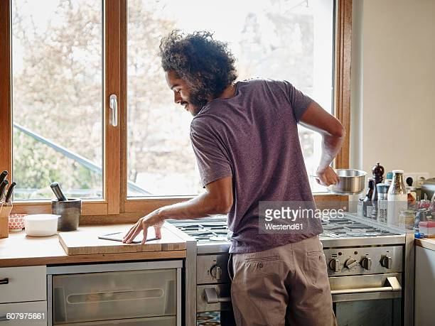 Young man standing at stove in kitchen checking digital tablet