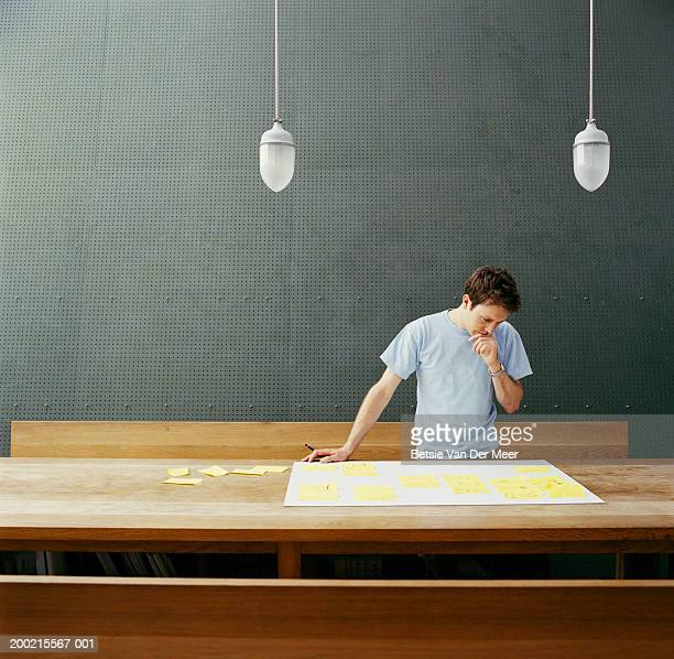 Young man standing at trestle table looking at notes