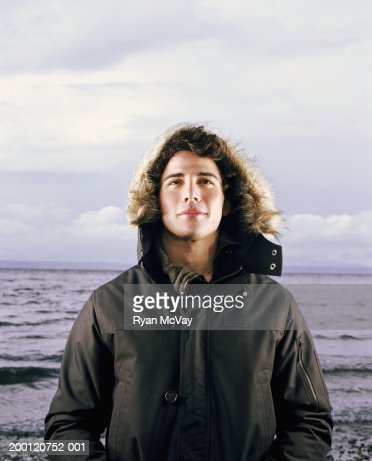Young man standing beside sea, wearing hooded jacket, portrait