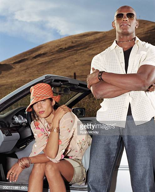 Young man standing beside woman in convertible car, portrait