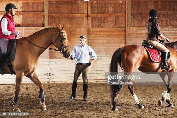Young man standing between to riders and their horses in a training stable, smiling
