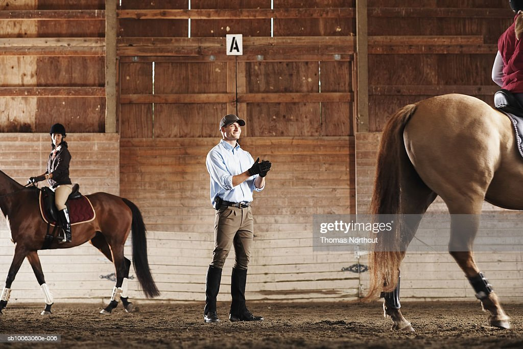Young man standing between to riders and their horses in a training stable, clapping : Stock Photo