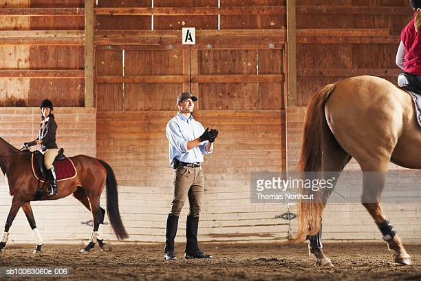 Young man standing between to riders and their horses in a training stable, clapping