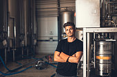 Portrait of young man standing by beer filling machine. Brewery worker with industrial equipment.