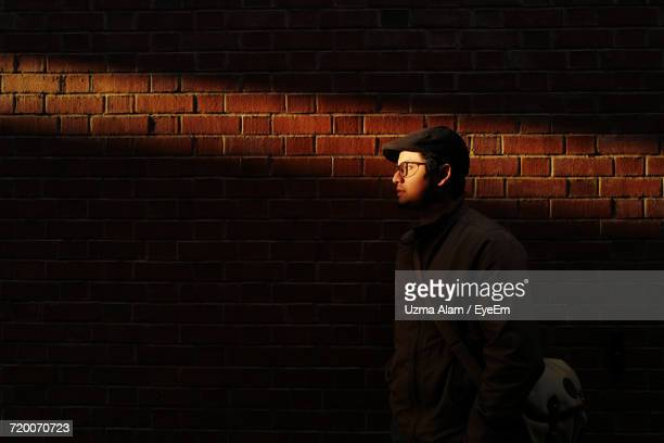 Young Man Standing By Brick Wall
