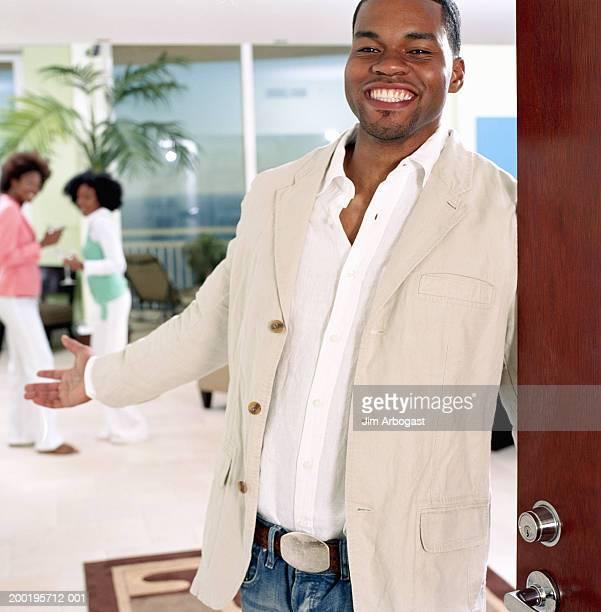 Young man standing by open door, smiling, portrait