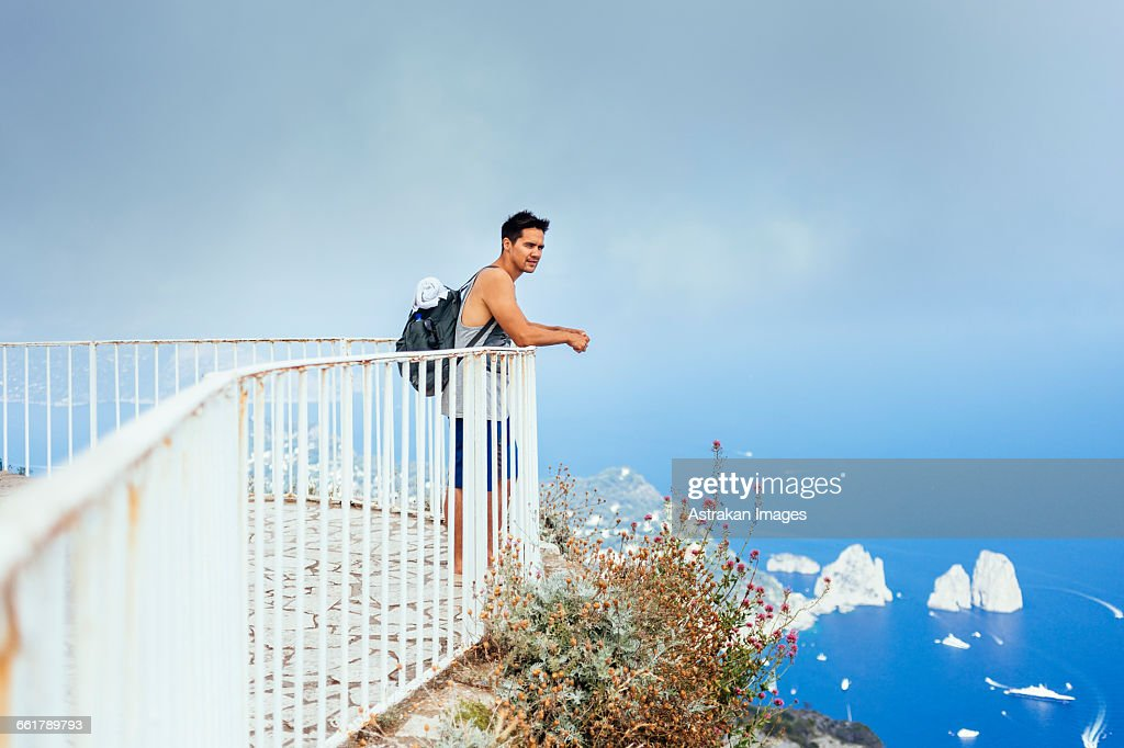 Young man standing by railing at observation point against sky