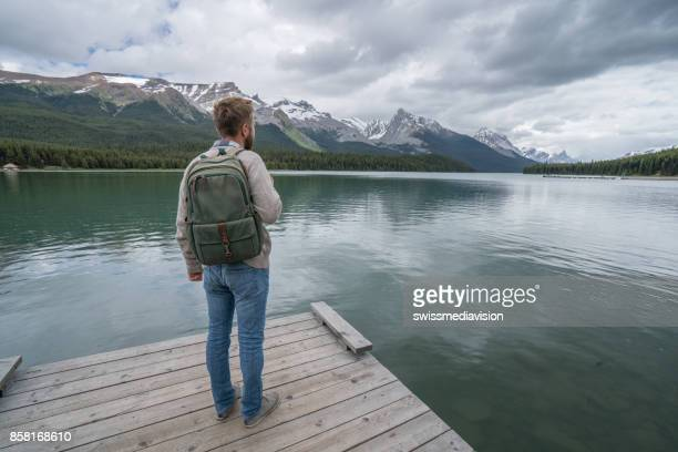 Young man standing by the lake looking at mountain scenery