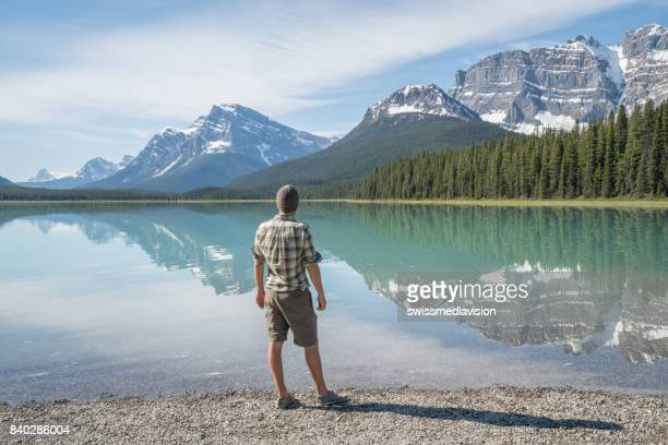 Young man standing by the mountain lake contemplating nature