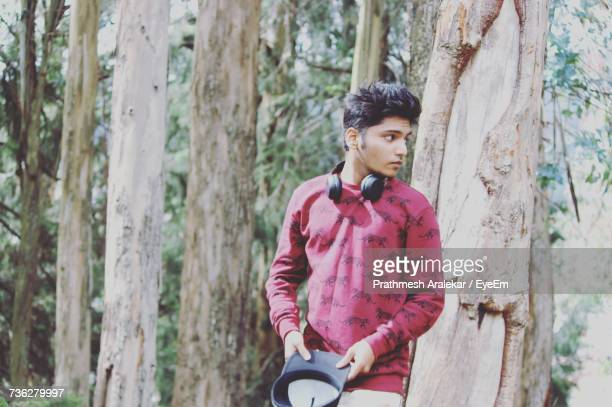 Young Man Standing By Tree Trunk