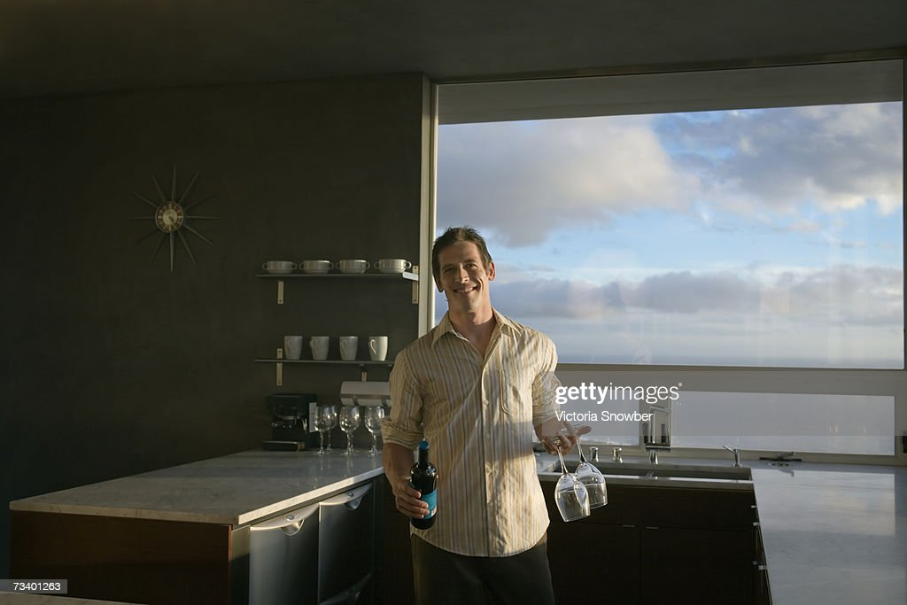 Young man standing holding bottle of wine and glasses, portrait : Stock Photo