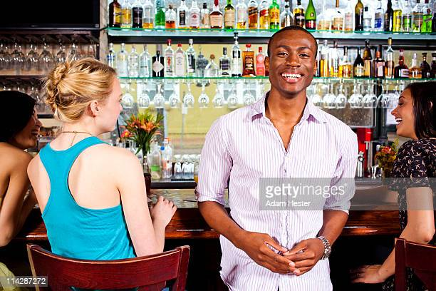 A young man standing in a bar with friends.