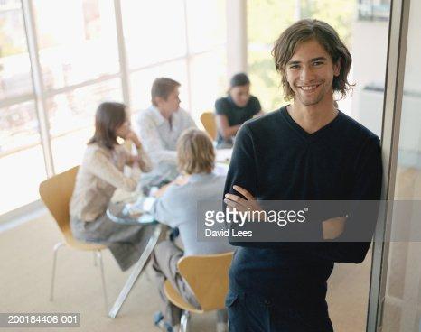 Young man standing in doorway of meeting room, smiling, portrait
