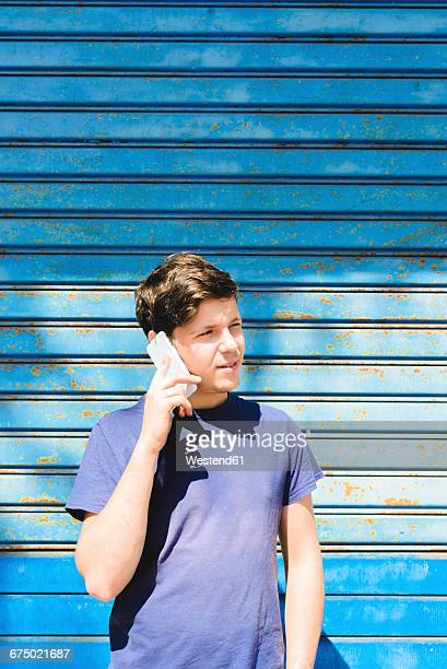 Young man standing in front of blue gate using smart phone